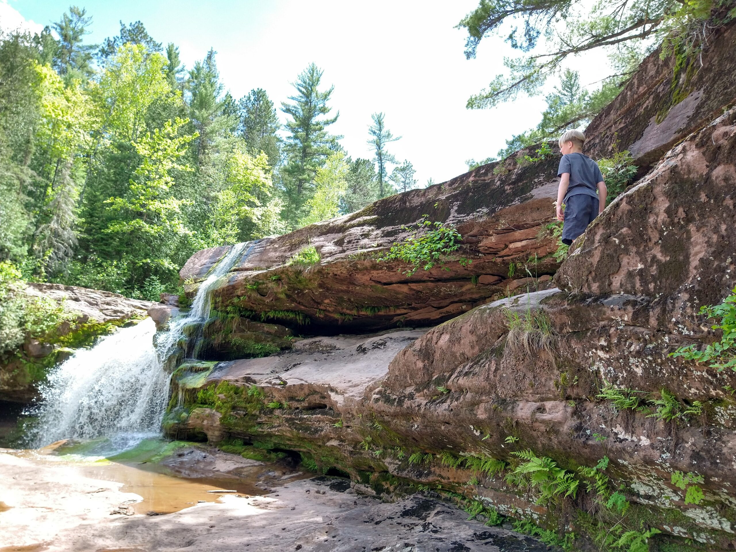 A child stands on a rock ledge, observing the waterfall.