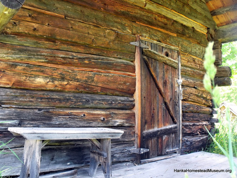 A rustic log cabin porch with a bench and door.