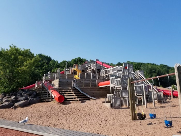 A giant playground structure on a sandy beach.