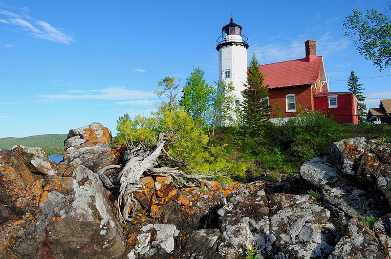 A lighthouse sits atop a rocky outcropping.